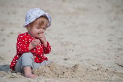 ребенок ест песок